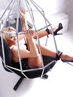 Naughty blonde Lucy Zara is bound by her ankles and forced to spread on a hanging metal swing chair
