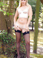 Gorgeous blonde Jana D poses outside in her dark stockings.