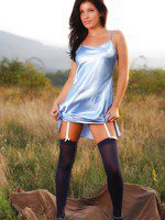 Louise strips out of her blue silk dress in a field to show off her underwear.
