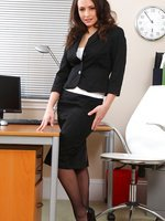 Sexy dark haired secretary teases her way out of her smart black skirt suit.