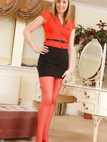 The lovely Claire Louise in a black miniskirt, tight red top and red stockings.