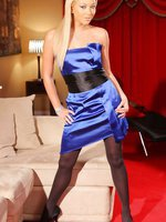 Pretty blonde in a blue, satin evening dress, stockings and heels.
