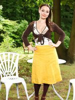 Brunette outside wearing a long, yellow skirt and brown top with brown pantyhose.