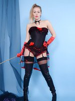 Sexy blonde dominatrix strips from high boots, corset and stockings.