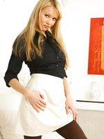 Sultry blonde in smart office outfit with lovely lingerie and dark tan stockings beneath.