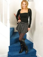 Saucy secretary Hayley-Marie in a revealing outfit with patterned grey pantyhose and kinky black boots.