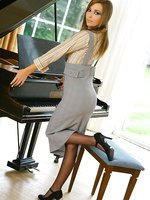 Stunning Loora strips out of her secretary outfit by her piano, revealing her sexy purple lingerie and stockings
