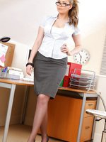 Long haired blonde looking gorgeous in a sexy secretary outfit.