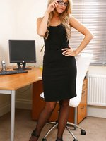 Stephanie wearing a black minidress in her office.