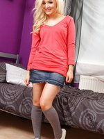 Cheeky blonde slips out of her cute, casual outfit and poses in nothing but her knee high grey socks.