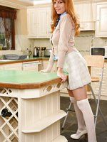 Stunning redhead Monika seductively removes miniskirt and sweater.