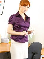 Saucy secretary in smart office outfit with light lingerie and stockings.