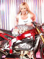 Blonde sweetheart, Rachel Aziani, looks amazing posing with the stunt bike in her tank top that shows off her big boobs and thigh-high black boots!