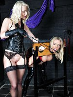Sexy blonde lesbian gags hot Milf in the stocks and gives her ass a good spanking