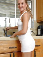 Spunky mature babe Sara James pulls off her wet t-shirt in the kitchen.