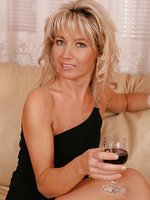 Older babe Janet Darling enjoys wine while fingering herself.